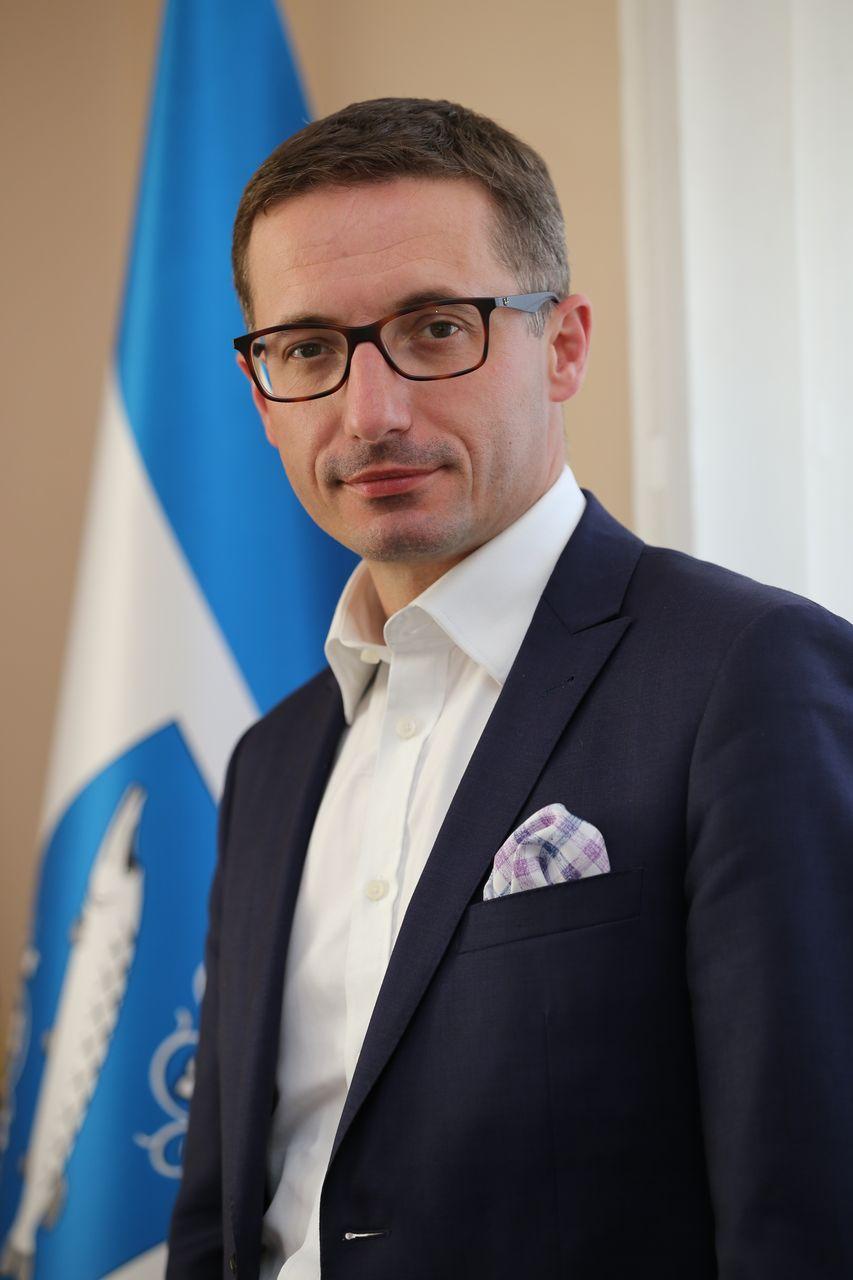 Prezydent Miasta Rybnika Piotr Kuczera na tle flagi Miasta
